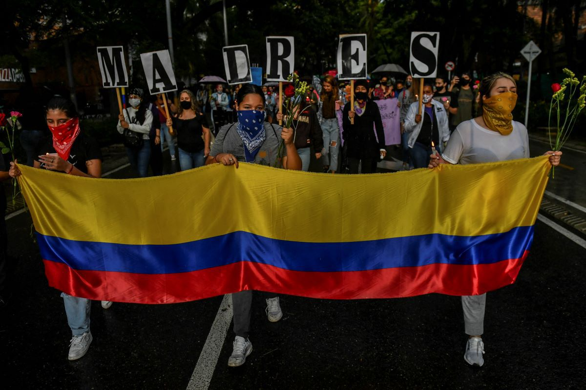 Women hold a Colombian flag and the letters that form the word