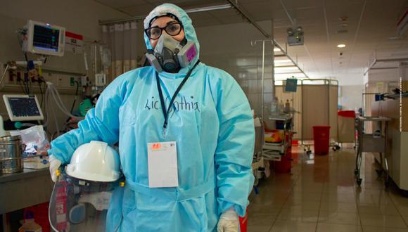 La licenciada Cynthia Pérez (36) trabaja en el área de emergencia del hospital de Ate Vitarte, con pacientes entubados. Su equipo de protección consiste en mascarilla 3M, cuatro prendas (uniforme, mameluco y dos mandilones), guantes descartables, tres gorros (de tela, quirúrgico y del mameluco) y un casco. Le ha dado infección urinaria y cistitis por retener la orina (salir del turno significa sacarse todo, botarlo a la basura y volver a vestirse; tiempo valioso que no puede perder). No toma agua un día antes del turno para evitar ir al baño. (Foto: Héctor Bartra - Hospital de Emergencia de Ate)