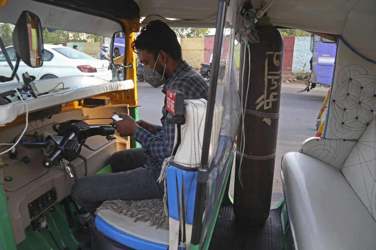 Mohammad Javed Khan turned his motorcycle into an ambulance by fitting an oxygen cylinder with accessories to treat coronavirus patients. (Photo: Gagan Nayar / AFP).