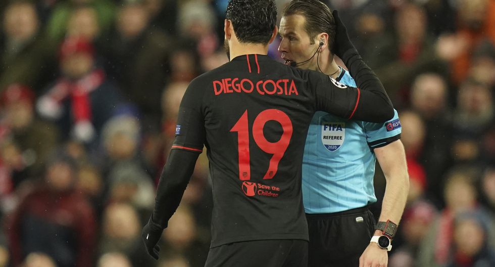 Referee Danny Makkelie, right, argues with Atletico Madrid's Diego Costa during a second leg, round of 16, Champions League soccer match between Liverpool and Atletico Madrid at Anfield stadium in Liverpool, England, Wednesday, March 11, 2020. (AP Photo/Jon Super)