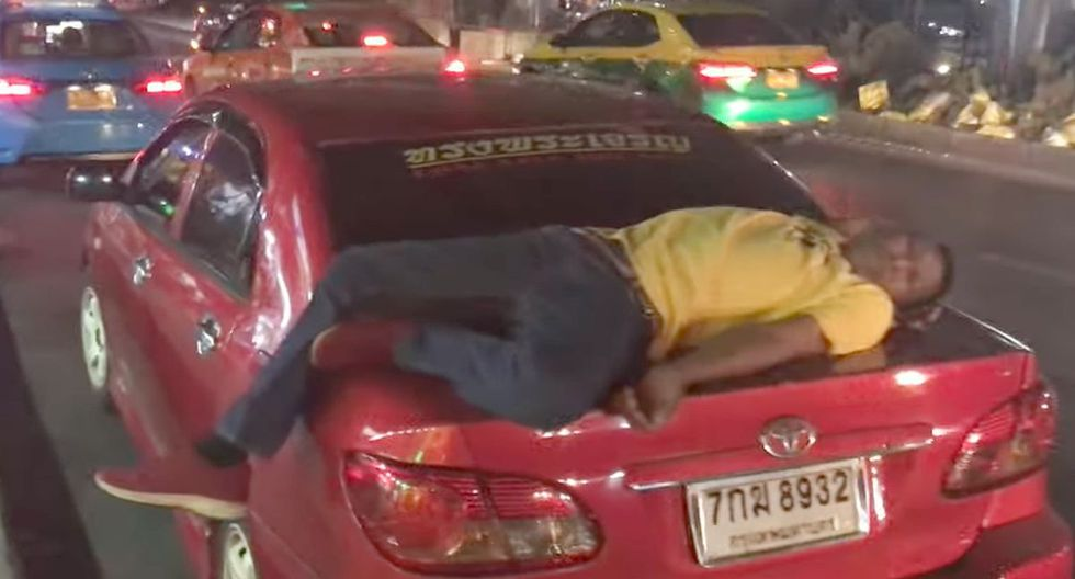 Un taxista se quedó dormido sobre la maletera de su vehículo en plena carretera en Bangkok, Tailandia | Foto: Captura de video YouTube / Viral Press