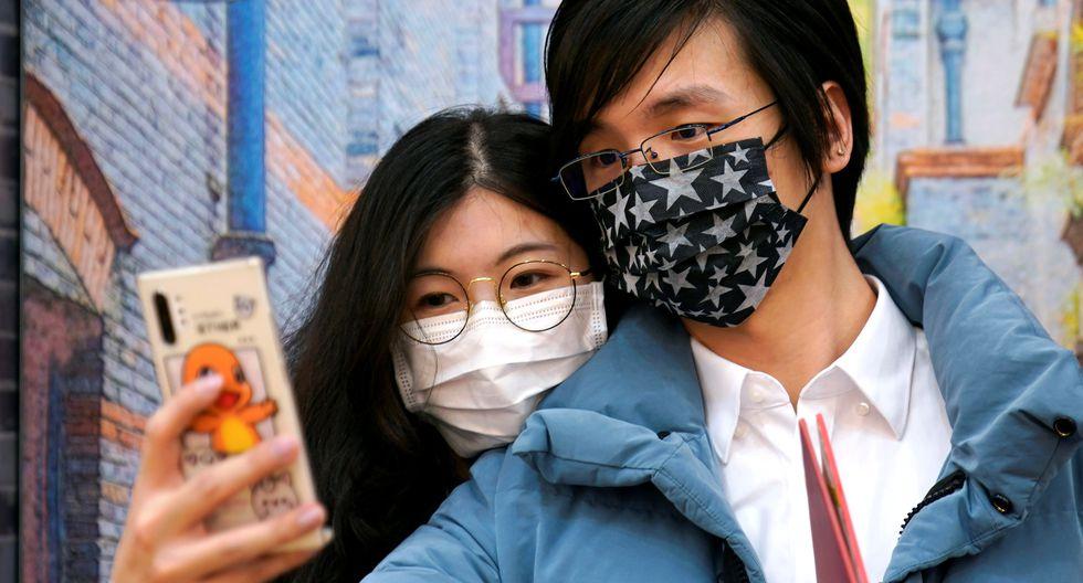 Wang, de 32 años, y su esposa Shi, de 30, son vistos con máscaras en una oficina de registro de matrimonios en el Día de San Valentín en Shanghai, China. (Foto: Reuters)