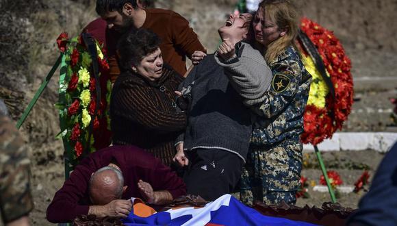 Una madre llora ante el ataúd con el cuerpo de su hijo en Stepanakert durante los combates por la región separatista de Nagorno-Karabaj el 17 de octubre de 2020. (Foto de ARIS MESSINIS / AFP).