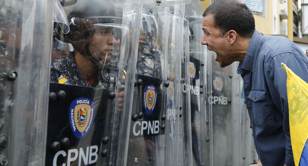 A protester yells at police blocking an opposition march in Caracas, Venezuela, Tuesday, March 10, 2020. U.S.-backed Venezuelan political leader Juan Guaido is leading a march aimed at retaking the National Assembly legislative building, which opposition lawmakers have been blocked from entering. (AP Photo/Ariana Cubillos)