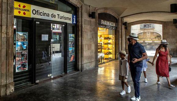 Coronavirus España: Una familia de visitantes camina ante una oficina de turismo cerrada en el centro de Barcelona este martes, cuando el sector turístico catalán se enfrenta a un nuevo parón, tras la leve reactivación que había vivido después de la apertura de fronteras, por las restricciones impuestas por países como Reino Unido a los turistas que vienen de España o las recomendaciones de Francia y Alemania de no viajar a Cataluña. (EFE/Enric Fontcuberta).