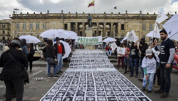 Las imágenes de personas desaparecidas y víctimas del conflicto armado se muestran durante una protesta frente al teatro Colón en Bogotá, mientras los miembros del gobierno colombiano y las FARC asisten a una ceremonia para conmemorar el primer aniversario del acuerdo de paz el 24 de noviembre de 2017.(Foto: AFP).
