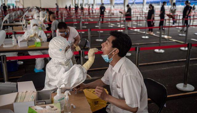 Personal de salud toma una prueba de hisopo a personas en una calle de Beijing (China). (AFP / NICOLAS ASFOURI).