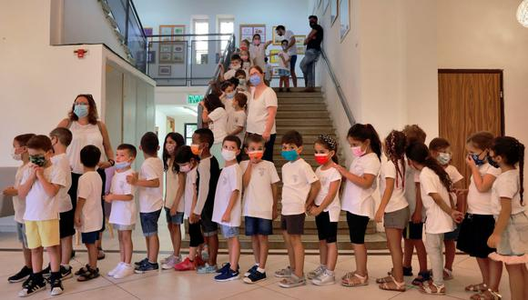 Una maestra israelí da la bienvenida a los alumnos que usan mascarillas protectoras a su regreso al nuevo año escolar en medio de un aumento de casos de coronavirus en Israel. (MENAHEM KAHANA / AFP).