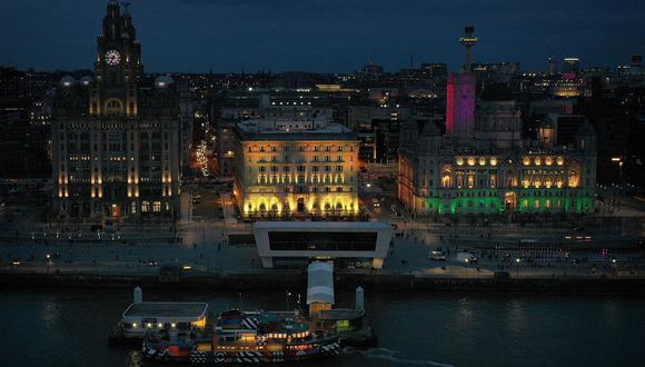 Esta fotografía de archivo tomada el 23 de marzo de 2021, muestra una vista aérea del Edificio Liver (izq.), el Edificio Cunard (centro) y el edificio del Puerto de Liverpool iluminados como parte del Día Nacional de Reflexión en Liverpool, noroeste de Inglaterra. (Paul ELLIS / AFP).