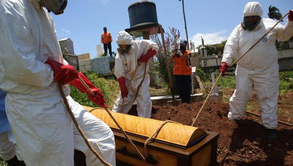 Miembros de Protección Civil vistiendo trajes de bioseguridad entierran el ataúd de una víctima del coronavirus COVID-19 en el cementerio Municipal de San Cristóbal, Venezuela. (Foto: Archivo/AFP / CARLOS EDUARDO RAMIREZ).