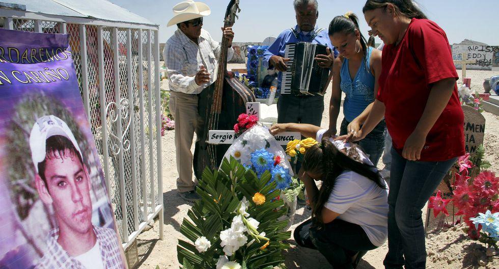 Los familiares consuelan a María Guadalupe Guereca mientras llora en la tumba de su hijo en Ciudad Juárez, México, en 2012 (Foto: EFE)