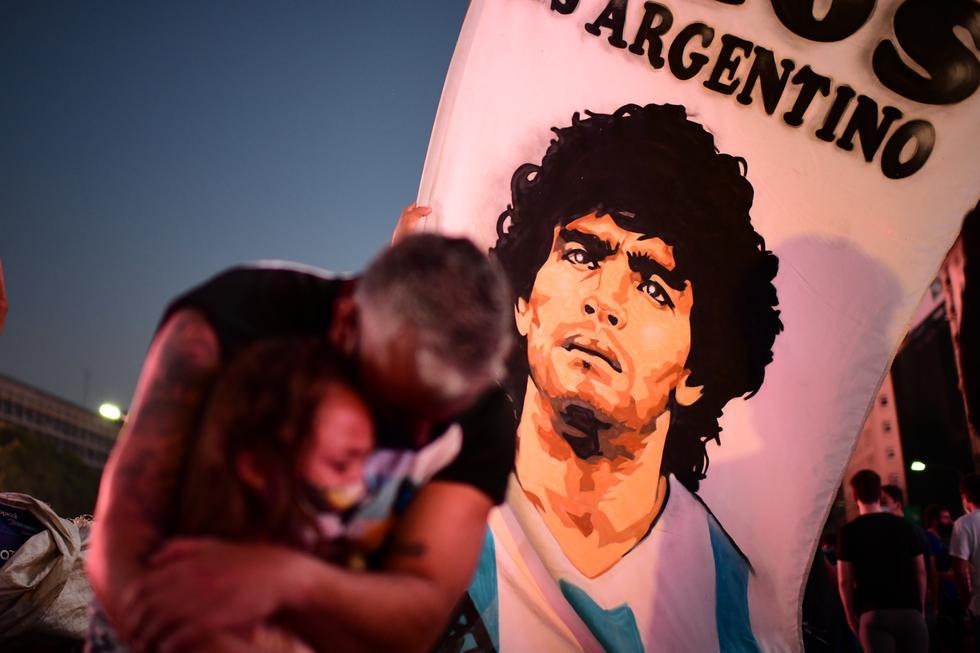 Un padre y su hija, fanáticos de la leyenda del fútbol argentino Diego Maradona, lloran mientras se reúnen junto al Obelisco para rendir homenaje el día de su muerte en Buenos Aires. El cuerpo permanecerá en el palacio presidencial durante tres días de duelo nacional, anunció la presidencia. (Foto: Ronaldo Schemidt / AFP)