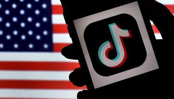 En esta ilustración de fotografía de archivo, el logotipo de la aplicación de redes sociales, TikTok, se muestra en la pantalla de un iPhone sobre un fondo de bandera estadounidense. (AFP/Olivier DOULIERY).