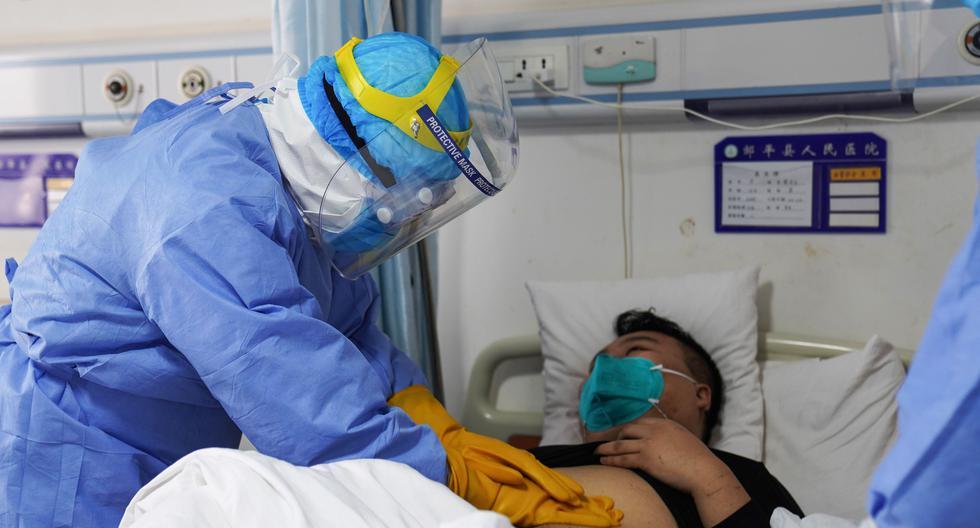 Esta foto tomada el 28 de enero del 2020 muestra a un médico revisando a un paciente infectado por el nuevo coronavirus en un hospital de China. (Foto referencial, AFP).