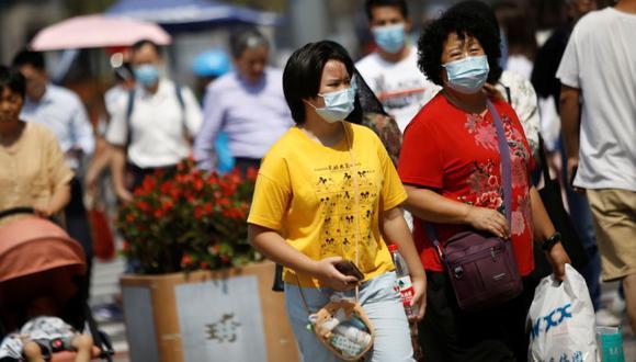 Personas que usan mascarillas caminan en un área comercial, después de que el Centro para la Prevención y el Control de Enfermedades de Beijing anunciara que el uso de mascarillas ya no es obligatorio al aire libre en Beijing, luego del brote de la enfermedad por coronavirus (COVID-19), China. (Foto: REUTERS / Tingshu Wang).