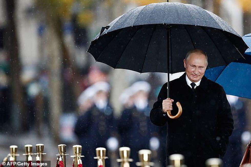 Vladimir Putin se protege de la lluvia. (AFP).