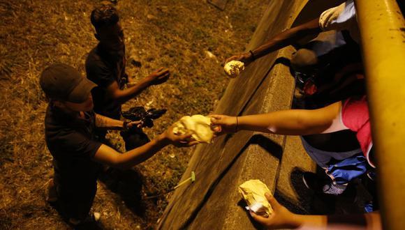 Solidaridad. Fotografía fechada el 23 de julio de 2020 que muestra a dos hombres que reciben alimentos en una calle de Cali (Colombia). Con solo unos pedales y cargados de comida en los morrales, una veintena de voluntarios de la fundación Bici Contra el Hambre combate el hambre al repartir decenas de raciones de comida a diario a los habitantes de calle y personas en situación vulnerable de la ciudad de Cali, en el oeste de Colombia. (EFE/Ernesto Guzman Jr).