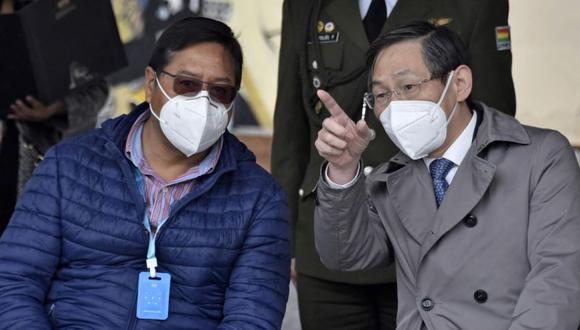 El presidente boliviano Luis Arce (izq.) Conversa con el embajador de China, Huang Yazhong, durante la entrega de 2 millones de mascarillas y un hospital militar de campaña donado por China para la lucha contra el nuevo coronavirus COVID-19, en El Alto. (Foto: AFP / Aizar RALDES).