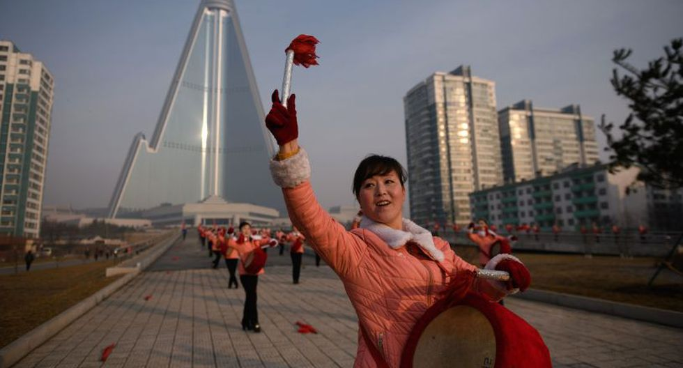 Motivan a los trabajadores de Pyongyang con banderas y tambores. (Foto: AFP)