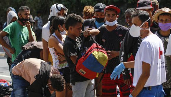 Los migrantes venezolanos usan mascarillas mientras hacen cola para recibir alimentos y medicamentos de miembros de la Cruz Roja en una carretera en Cúcuta, Colombia, en la frontera con Venezuela en medio de la pandemia de COVID-19. (Foto: Schneyder MENDOZA / AFP).