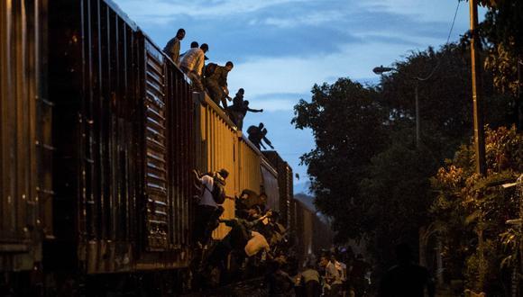 """Migrantes indocumentados suben a un tren conocido como """"La Bestia"""", en la localidad de Las Patronas, estado de Veracruz, México, el 9 de agosto de 2018 para llegar a Estados Unidos. (Foto de RONALDO SCHEMIDT / AFP)."""