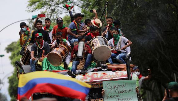 Personas al costado de la carretera saludan a los indígenas colombianos mientras viajan en un autobús a sus resguardos indígenas, en Cali, Colombia. (Foto: REUTERS / Luisa Gonzalez).