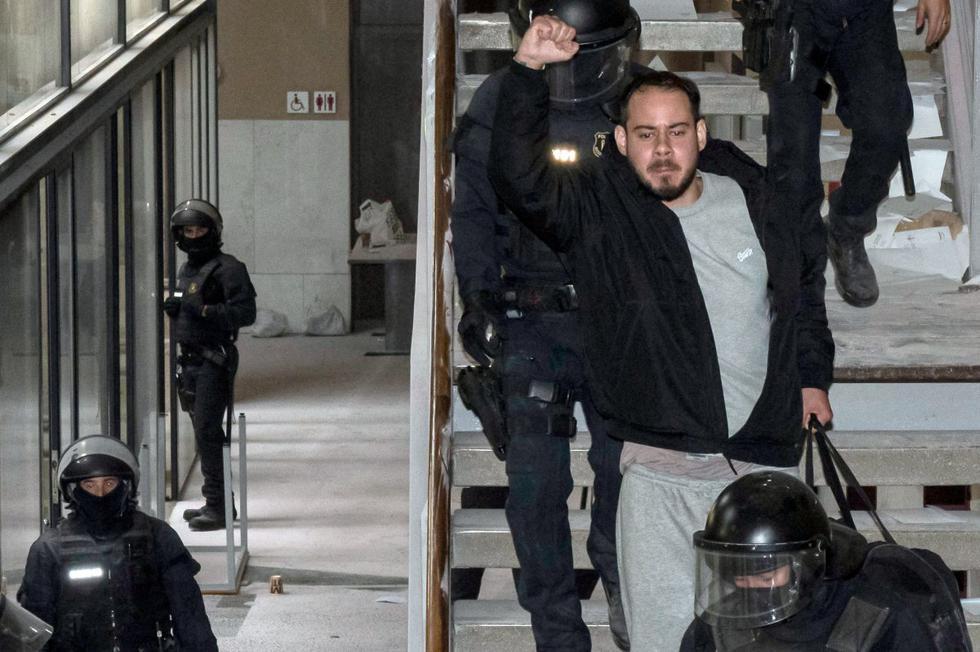 """""""¡No nos van a parar nunca, no nos van a doblegar!"""", gritaba con el puño alto Hasél mientras la policía lo escoltaba fuera de la universidad de Lérida, en la región nororiental de Cataluña, donde se había atrincherado la víspera con decenas de jóvenes. (Foto: J. Martin / AFP)"""