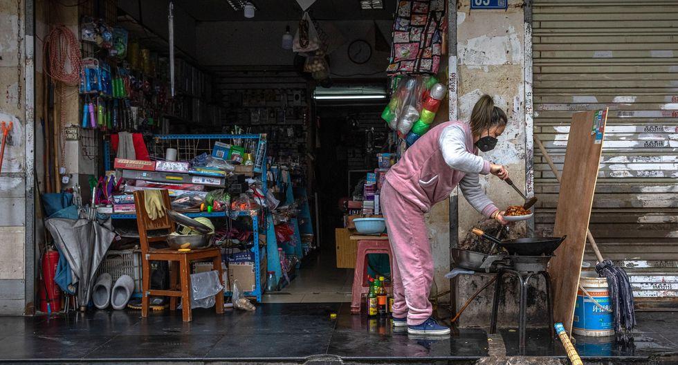 Una mujer que usa máscara facial protectora cocina junto a una tienda en Wuhan. (EFE / EPA / ROMAN PILIPEY).
