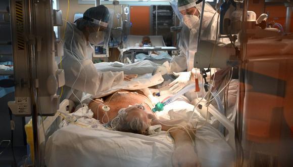 Médicos con equipo de protección personal (EPP) atienden a un paciente en la Unidad de Cuidados Intensivos (UCI) de nivel 3 de para casos de coronavirus, COVID-19 en el hospital Casal Palocco, cerca de Roma, el 22 de octubre de 2020. (Foto de Alberto PIZZOLI / AFP).