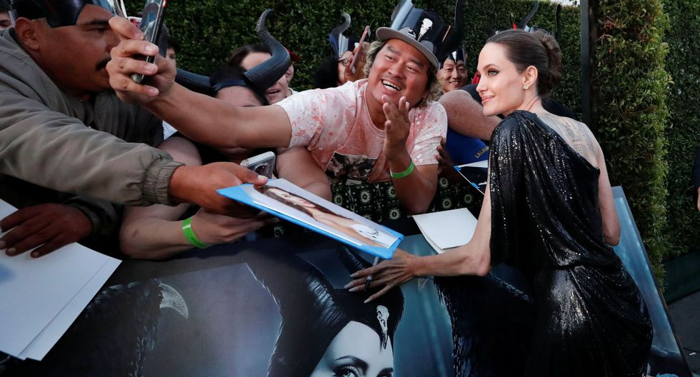 """Actor Angelina Jolie poses with a fan before the premiere of """"Maleficent: Mistress of Evil"""" in Los Angeles, California, U.S., September 30, 2019.  REUTERS/Mario Anzuoni"""