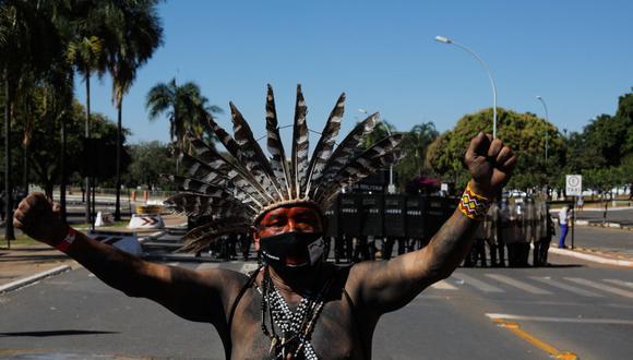 Indígenas protestan frente a una línea de policías antidisturbios cerca del  Congreso de Brasil. (Foto de Sergio Lima / AFP).