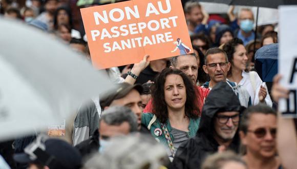 """Una mujer sostiene un cartel que dice """"NO al pase sanitario"""", durante una manifestación contra la vacunación obligatoria para ciertos trabajadores y el uso obligatorio del pase de salud convocada por el gobierno francés, en Nantes, oeste de Francia, el 24 de julio de 2021. (Sebastien SALOM-GOMIS / AFP)"""