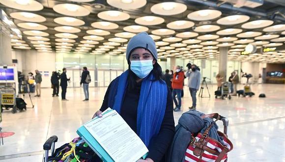 Una joven muestra el resultado de su PCR a su llegada al aeropuerto Adolfo Suárez-Barajas en Madrid, este lunes, donde comienza la exigencia de pruebas de coronavirus para pasajeros de vuelos procedentes de países de riesgo. (EFE/ Fernando Villar).