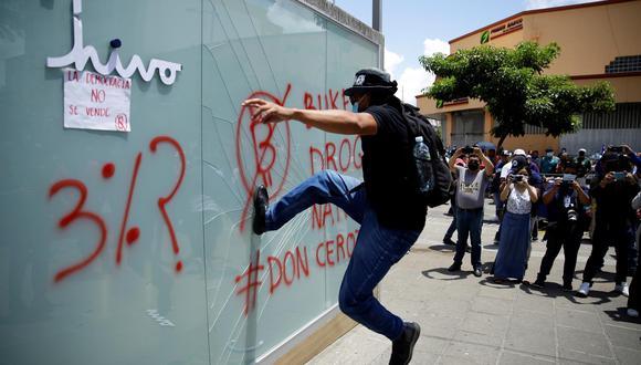 Manifestantes destruyen un kiosko de cajeros de la aplicación Chivo, recientemente instalados para canjear bitcóis por dólares, durante una jornada de protestas contra el Gobierno de Nayib Bukele en El Salvador. (EFE/ Rodrigo Sura).