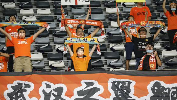 Los hinchas de Wuhan Zall animan al equipo durante el partido de fútbol de la Superliga de China (CSL) entre Wuhan Zall y Beijing Guoan en Suzhou. (Foto de STR / AFP) / China OUT).