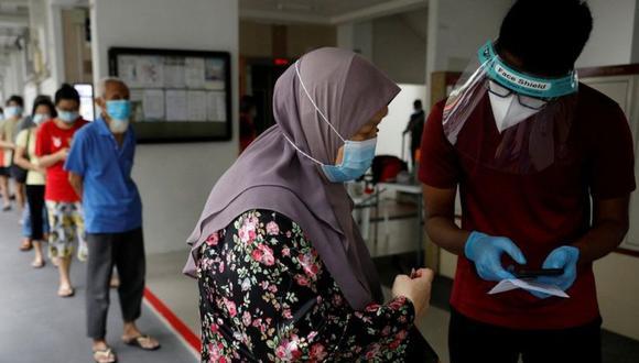 Los residentes de una urbanización pública hacen cola para las pruebas obligatorias de coronavirus en Singapur el 21 de mayo de 2021. (REUTERS)