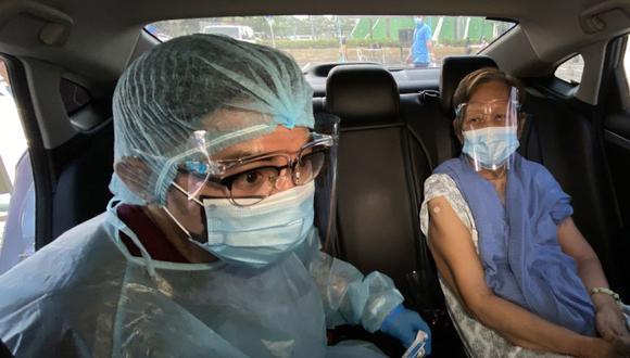 Una anciana filipina (derecho) recibe su dosis de una vacuna COVID-19 dentro de un vehículo en un centro de vacunación drive-thru en la ciudad de Makati, Metro Manila, Filipinas. (Foto: EFE / EPA / FRANCIS R. MALASIG).