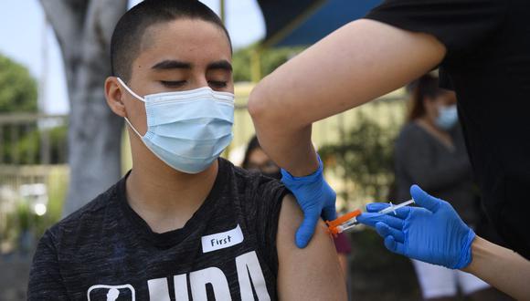 Héctor Garnica, de 13 años, recibe una primera dosis de la vacuna Pfizer contra el coronavirus Covid-19 en Los Ángeles, Estados Unidos. (Foto de Patrick T.FALLON / AFP).