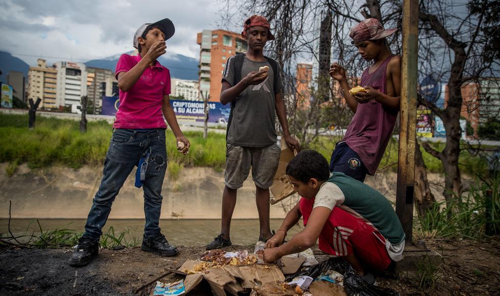 Un grupo de niños busca comida entre bolsas de basura que obtuvieron en una panadería de Caracas, capital de Venezuela. (Miguel Gutiérrez / EFE).