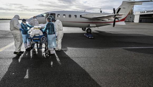 Personal médico transporta a un paciente a una avioneta para ser llevado a otro hospital cerca de Lyon, sureste de Francia, el 16 de noviembre de 2020. (Foto de Philippe DESMAZES / POOL / AFP).