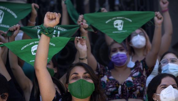 Activistas feministas sostienen pañuelos verdes durante una manifestación en favor de la despenalización del aborto en Chile.  (Foto de CLAUDIO REYES / AFP).
