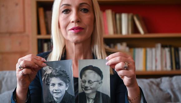 Valerie Portheret, historiadora y escritora, posa con fotografías de niños salvados en agosto de 1942, en Lyon, centro-este de Francia. (Foto de Philippe DESMAZES / AFP).