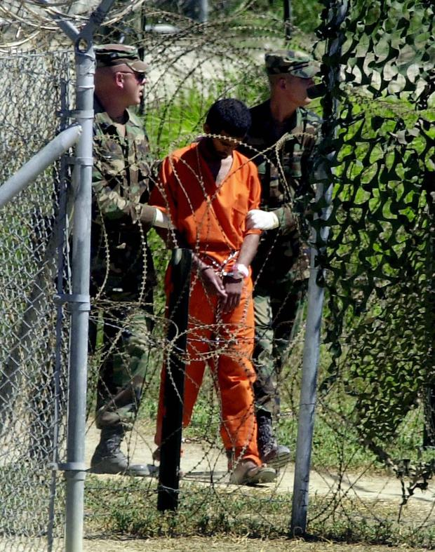 A photo taken on March 2, 2002 shows a prisoner being taken to an X-ray camp in Guantanamo Bay, Cuba.  (AFP photo / Peter Mahli).