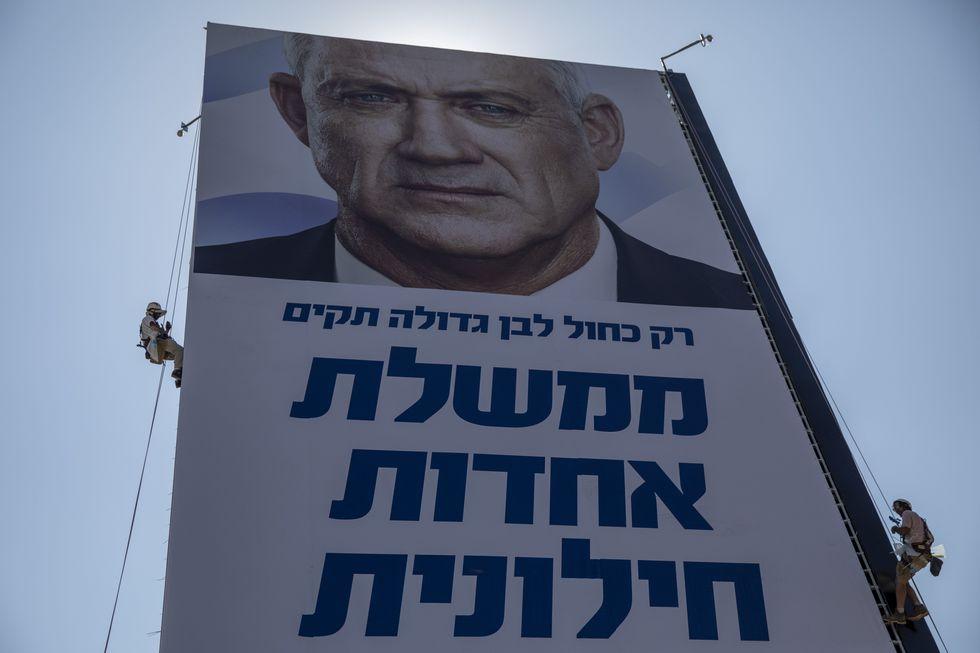 Un trabajador cuelga una publicidad electoral del líder Benny Gantz. (Foto: AP)