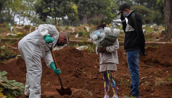 Un empleado del cementerio de Vila Formosa, en las afueras de Sao Paulo, excava junto a familiares de una persona que murió por coronavirus. (Foto de NELSON ALMEIDA / AFP).