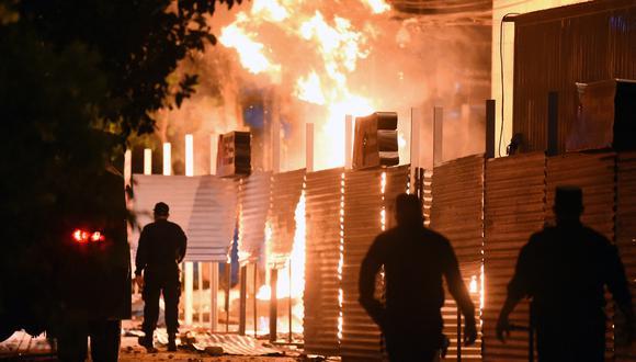 Policías son vistos cerca de un incendio provocado por manifestantes en la sede del Ministerio de Comercio de Paraguay. (NORBERTO DUARTE / AFP).