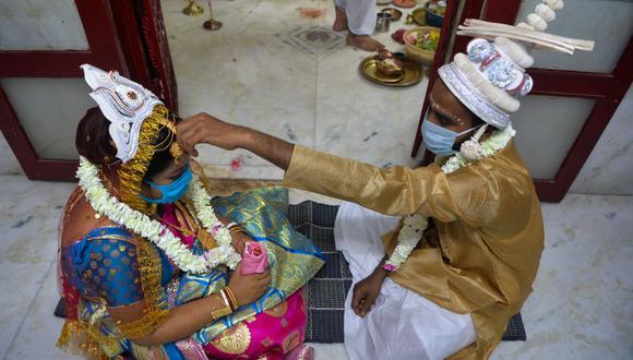 En esta foto referencial, Sanjib Mandal (derecha) y su novia Soma Roy usan mascarillas faciales mientras realizan rituales en su ceremonia de matrimonio en un templo hindú en plena pandemia de coronavirus. (Foto: DIPTENDU DUTTA / AFP).