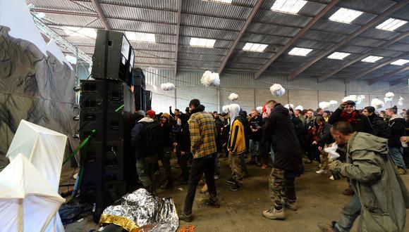 La gente baila durante una fiesta clandestina en un hangar en desuso en Lieuron, a unos 40 km al sur de Rennes, el 1 de enero de 2021. (Foto de JEAN-FRANCOIS MONIER / AFP).