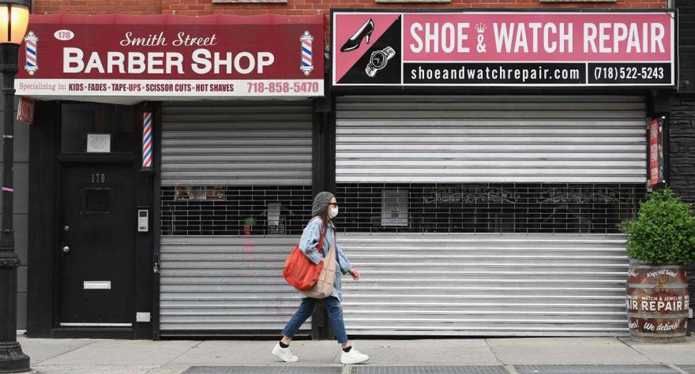 Esta foto del 5 de mayo muestra a una mujer caminando por negocios cerrados en Brooklyn, Nueva York. Las medidas de cierre en la ciudad se han extendido hasta el 13 de junio bajo una orden ejecutiva firmada por el gobernador estatal Andrew Cuomo. (Foto: AFP / Angela Weiss)