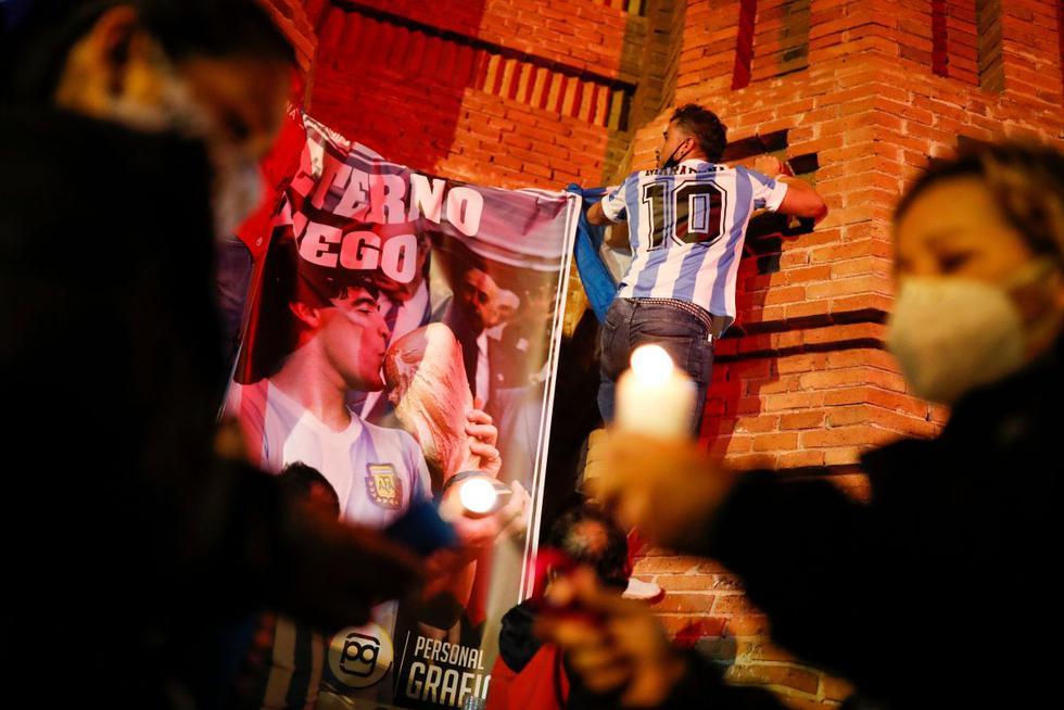 """Los fanáticos del fútbol encienden velas junto a un cartel con la imagen del fallecido leyenda del fútbol argentino Diego Armando Maradona leyendo """"Diego Eterno"""" para rendirle homenaje el día después de su muerte.  (REUTERS/Nacho Doce)."""